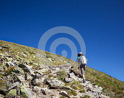 Woman hiking, on mountain trail