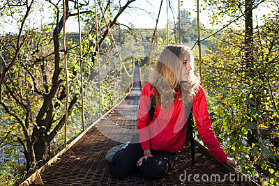 Woman hiking resting on the suspension bridge