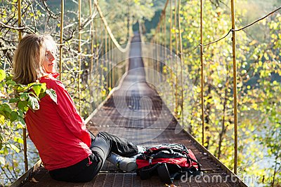 Woman hiking sitting in suspension bridge