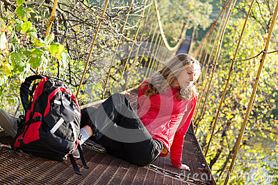 Woman hiking in suspension bridge and resting