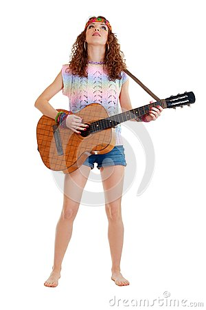 Woman in hippie outfit standing with guitar