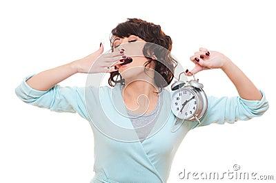 Woman holding alarm clock and yawning