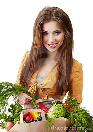 Woman holding a bag full of healthy food.
