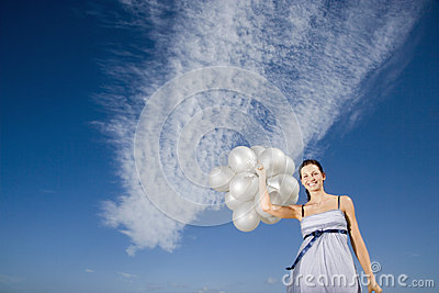 Woman Holding Balloons Against Sky