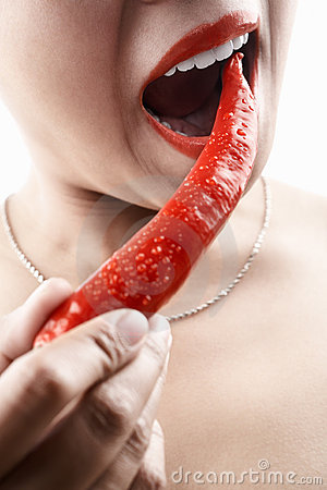 Woman holding big red chili in front of her mouth