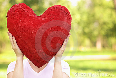 Woman holding big red heart before her face