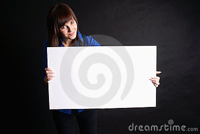 Woman holding blank board on black background.