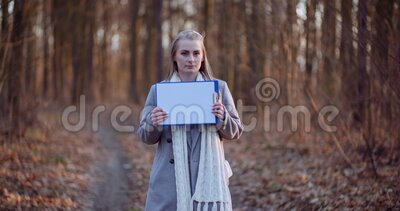 Woman holding blank paper in front of camera. Outdoors stock video footage