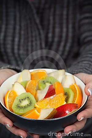 Woman holding bowl of fresh fruit