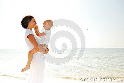 Woman holding boy on beach