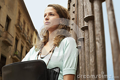 Woman Holding Briefcase Leaning Against Railing