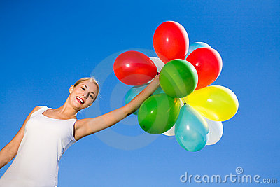 Woman holding bunch of balloons