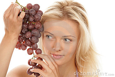Woman holding bunch of red grapes