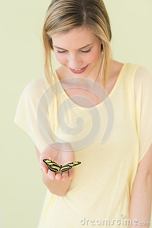Woman Holding Butterfly In Palm Against Colored Background