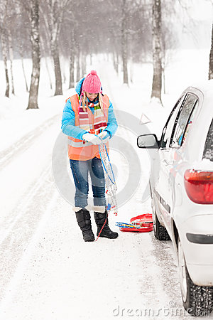 Woman holding car chains winter tire snow