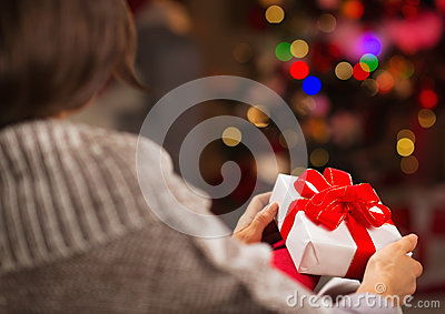 Woman holding Christmas present box. Rear view