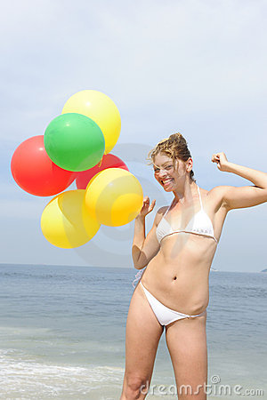 Woman holding colorful balloons on the beach