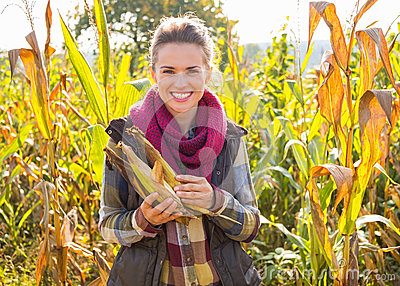 Woman Holding Corn While Standing In Cornfield Stock Photo ...