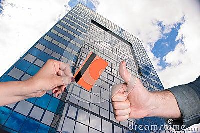 Woman holding credit card, man gesturing thumb up