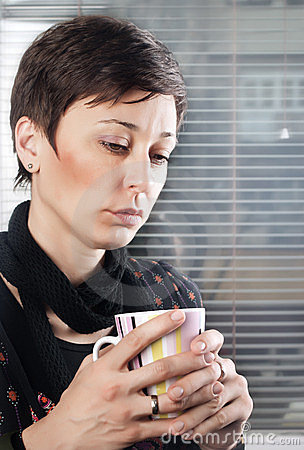 Woman holding a cup of black coffee