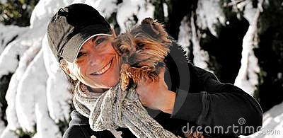Woman holding a dog in the snow