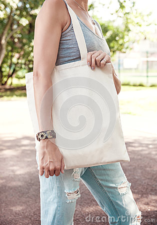 Free Woman Holding Empty Canvas Bag. Template Mock Up Stock Photos - 75752883