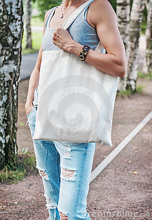 Free Woman Holding Empty Canvas Bag. Template Mock Up Stock Photos - 75752893