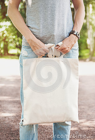 Free Woman Holding Empty Canvas Bag. Template Mock Up Royalty Free Stock Photo - 76624705