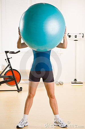 Woman holding exercise ball in health club