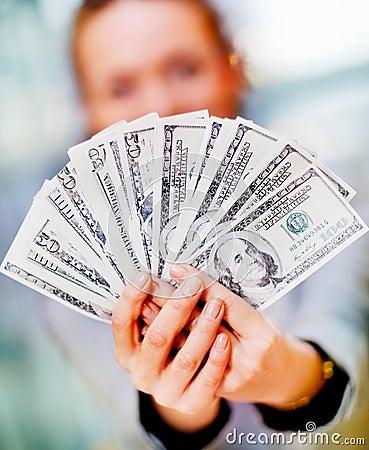 Woman holding a fan of hundred dollar bills