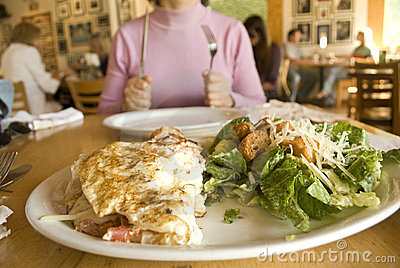 Woman holding fork and knife ready to eat omelet