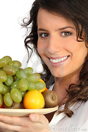 A woman holding a fruits plate