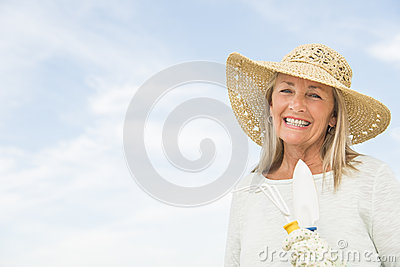 Woman Holding Gardening Equipment Against Sky