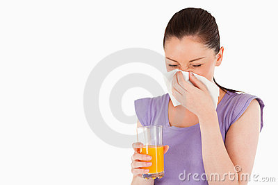 Woman holding a glass of orange juice and sneezing