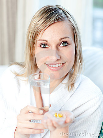 Woman holding a glass of water and pills