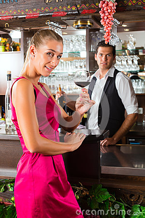 Woman holding a glass of wine in hand at the bar