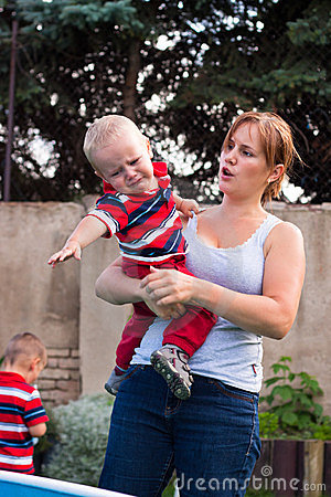 Woman holding grumpy crying toddler boy outdoors