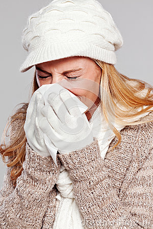 Woman holding a handkerchief and blowing her nose