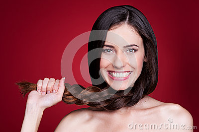 Woman holding her braid and smiling