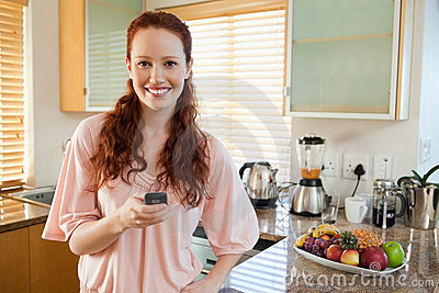 Woman holding her cellphone in the kitchen