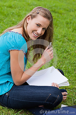Woman holding her pen while looking at the camera