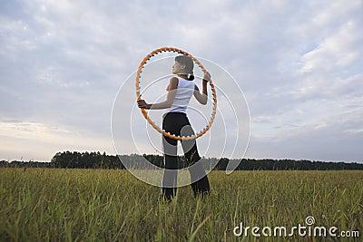 Woman Holding Hula Hoop On Field