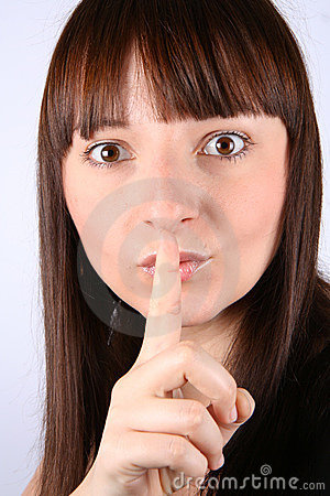 Woman holding index finger to her lips