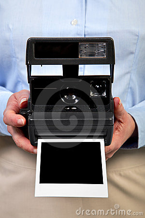 Woman holding instant camera blank frame.