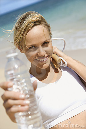 Woman holding jump rope and water bottle.