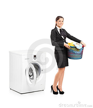 Woman holding a laundry basket next to a machine