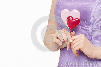 Woman holding lollipop in heart shape