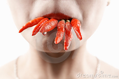 Woman holding lot of red chilies with mouth