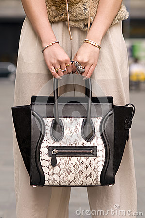 Woman holding purse, handbag with rings on fingers