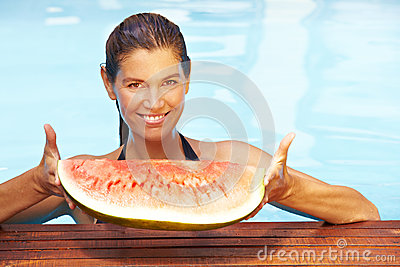 Woman holding melon in pool